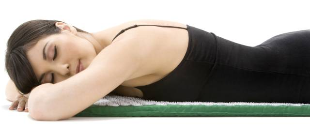 Lady lying face down on an acupressure mat